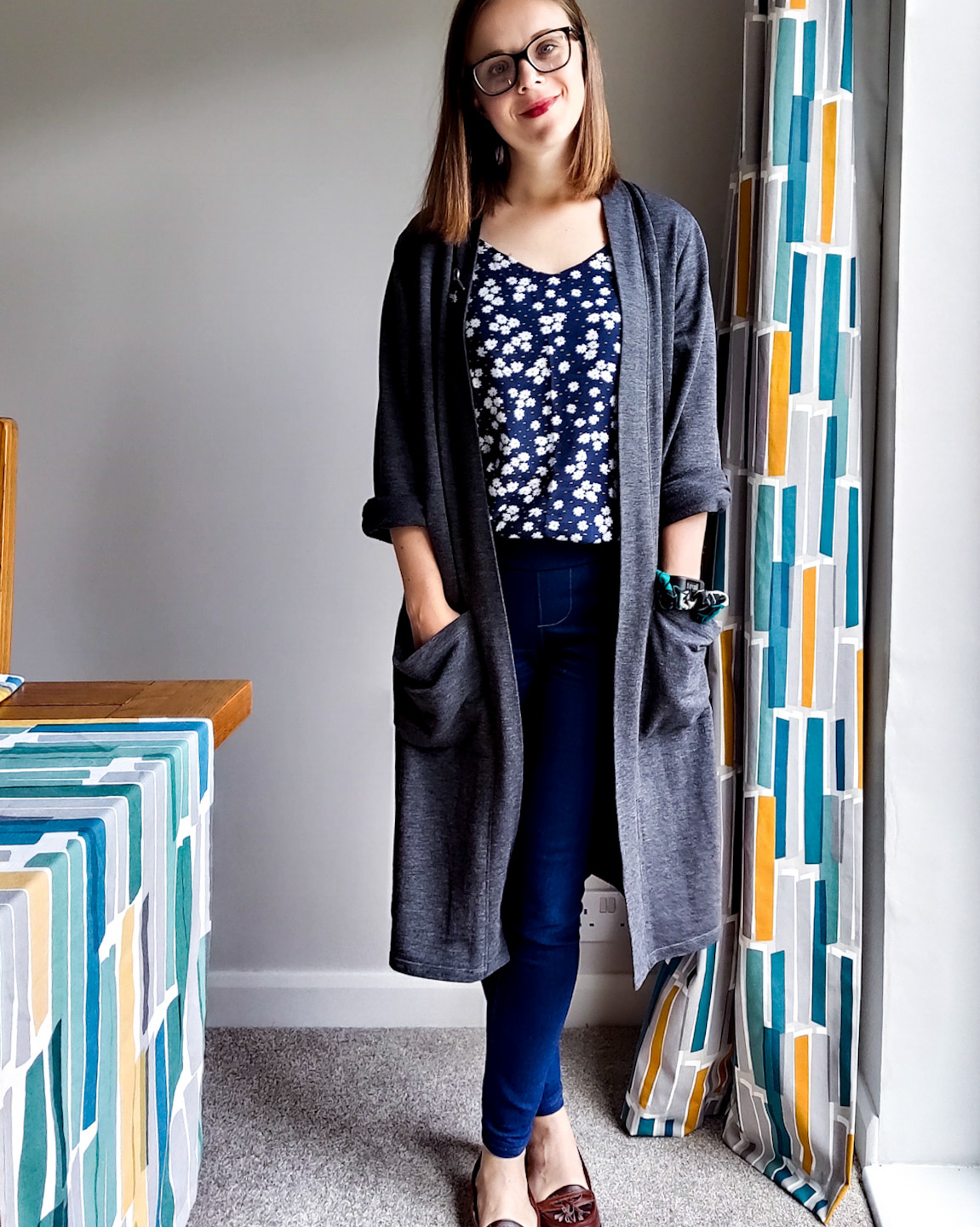 Helen is stood looking towaard the camera with her hands in her pockets. She is wearing blue denim SOS pants, a blue ogden cami and a grey knee-length kinder cardigan
