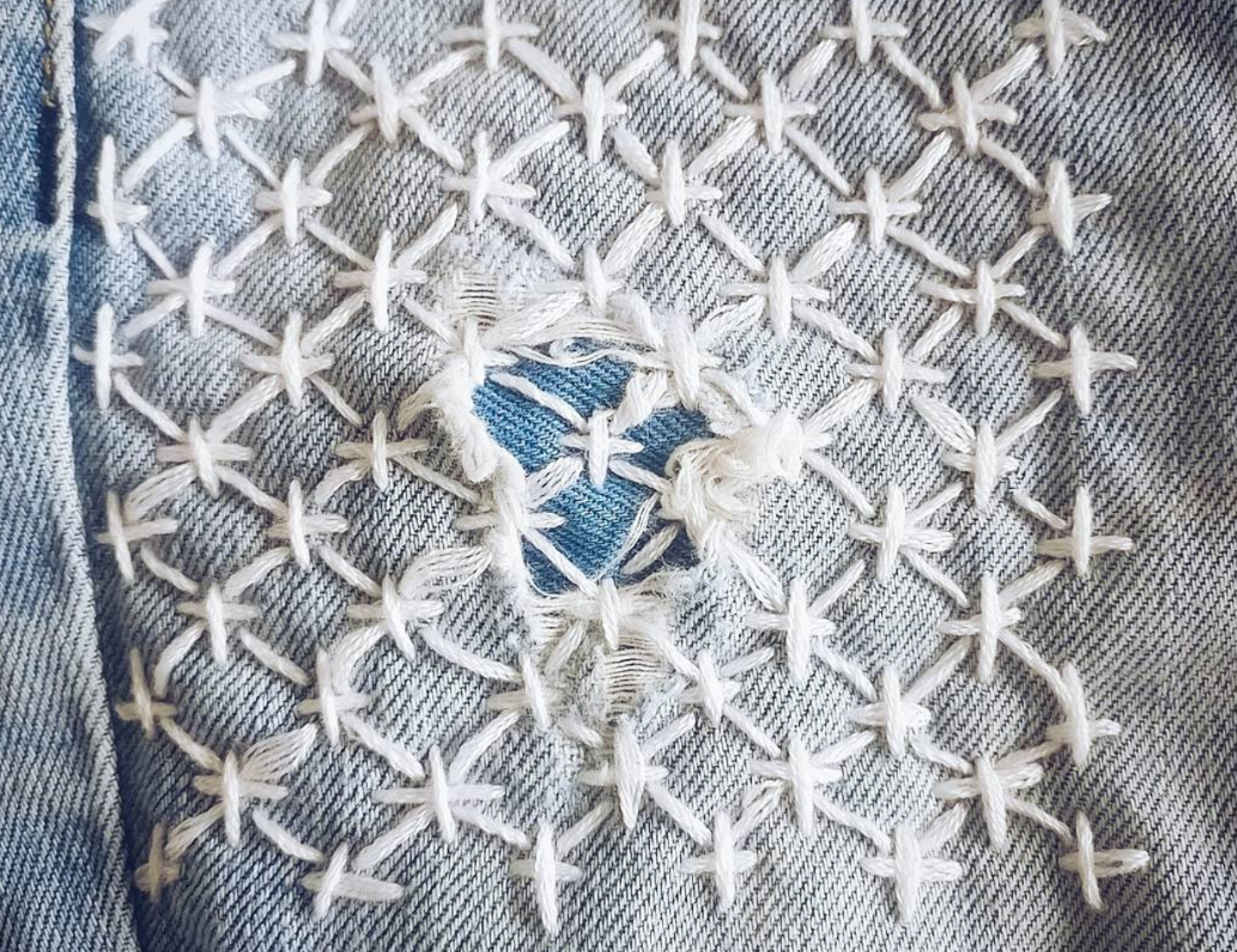 Ripped jeans patched up and mended using sashiko stitching